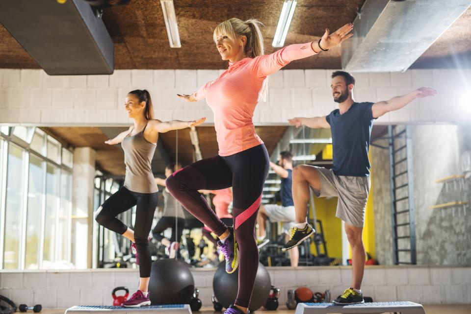 three trainers doing balance training in a gym